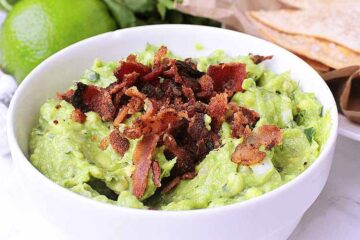 A white bowl with Keto Guacamole, garnished with crisp bacon.