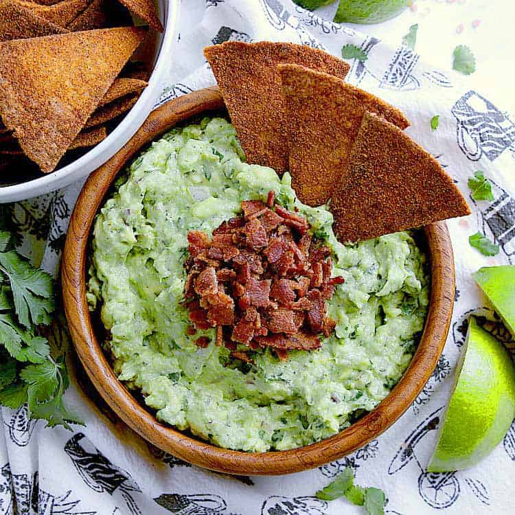 wooden bowl with Keto Guacamole, garnished with bacon and Keto Nacho Chips.