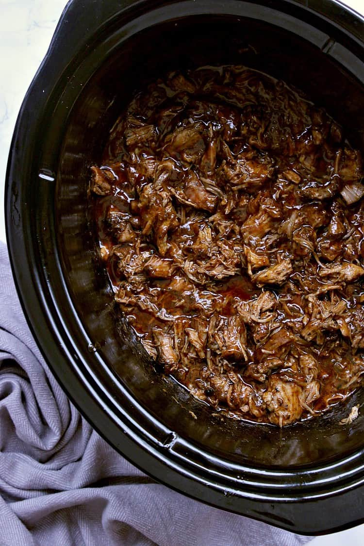 Slow cooker with pulled pork smothered in bbq sauce, ready to be served.