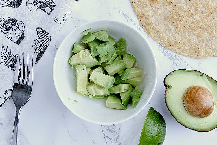 Bowl with half an avocado, beside a tortilla, half an avocado, a lime wedge and a fork.