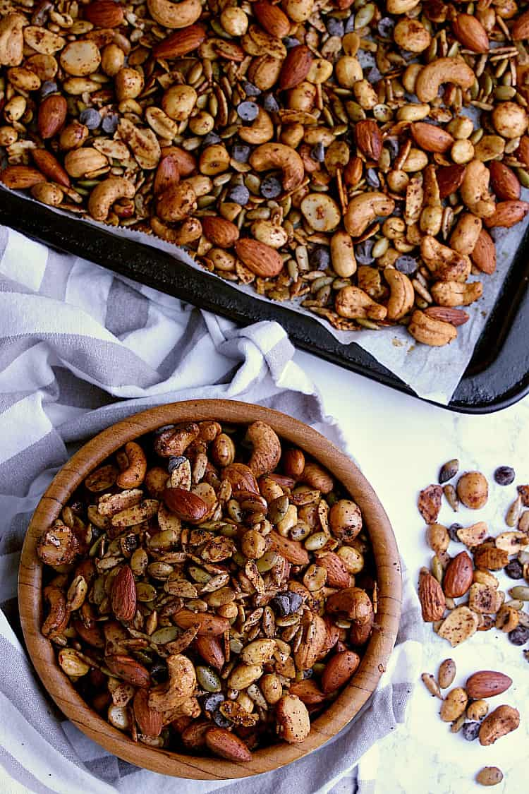 A wooden bowl of keto trail mix beside a baking sheet filled with the mix.