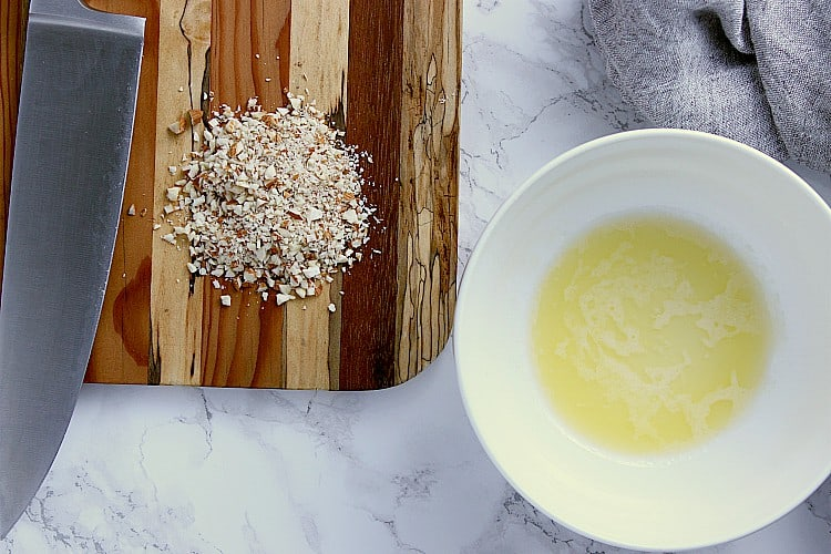 A bowl with melted butter next to a wooden cutting board with minced almonds and a knife.