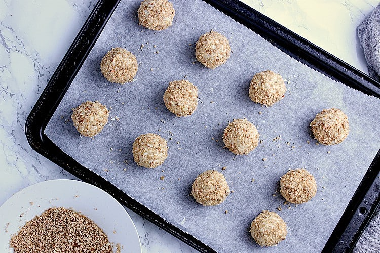 Baking sheet with Lemon Fat Bombs coated in cookie crust, next to a dish with leftover cookie crumble.