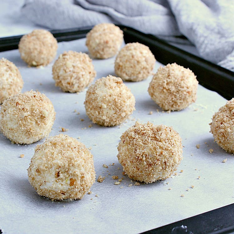 Baking sheet with a dozen lemon fat bombs, coated with cookie crust.