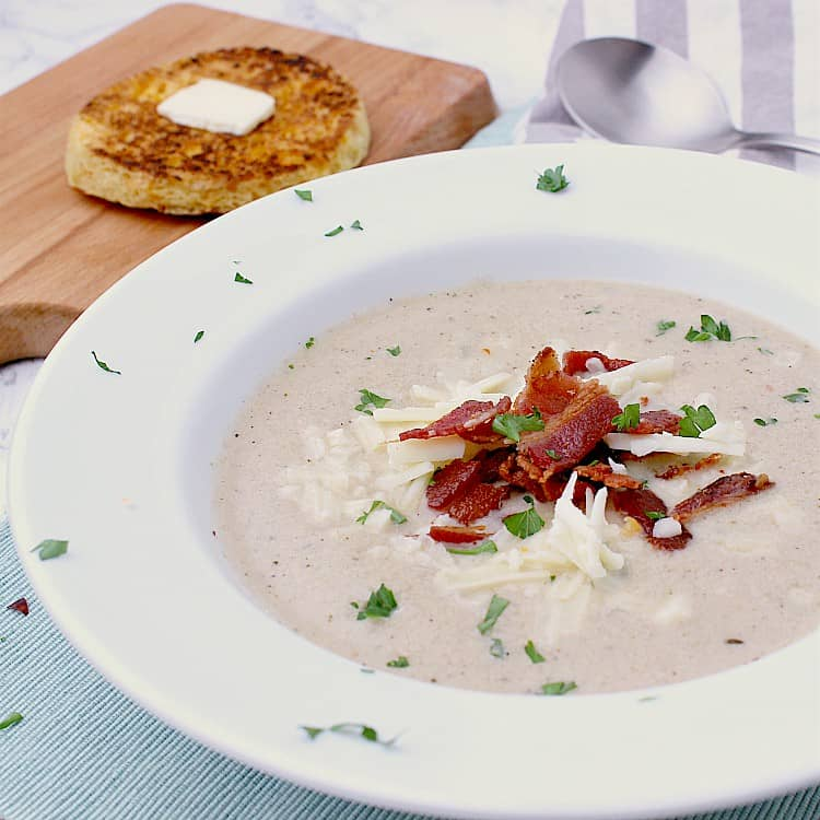 White bowl filled with Keto Cauliflower Soup and garnished with grated cheddar, crisp, crumbled bacon and minced parsley. A spoon is on the side of the bowl and some bread behind.     Saving Preview Publish   40/100    Add title *Updated - Creamy Keto Cauliflower Soup with Cheddar & Bacon On the table in 40 minutes, this Keto Cauliflower Soup is a great meal for busy days. It's loaded with crisp bacon and sharp cheddar, and is a dish the whole family will love!  READ MORE At no additional cost to you, I may make a small commission for purchases made through links in this post.  This post was originally published on September 26, 2018 and has been updated with with fresh images and content, though the recipe remains perfectly the same. Bacon. Cheese. Creamy cauliflower goodness. All in one bowl! This Keto Cauliflower Chowder was written a couple of years ago and it is still just as delicious today as it was then.   I'm bringing it back to the top for all of those who are new to Mama Bear's Cookbook, so that you may enjoy a bowl of hot, tasty Low Carb Cauliflower Soup this fall. I hope you love it as much as we do! Why it works Make it in 40 minutes without a ton of prep for an easy weeknight meal that is perfect for busy days. Crazy delicious, this ultra creamy Keto Cauliflower Soup is loaded with sharp cheddar and crisp bacon! An easy way to get your veggies in, this soup is healthy and packed with nutrients. Great for leftovers, Cauliflower Bacon Soup warms up great and freezes perfectly! Ingredients Chicken Broth - Use homemade chicken broth like this Instant Pot Chicken Broth, or buy organic chicken broth with as little additives as possible.  Cheddar - I prefer sharp aged white cheddar for this Keto Cauliflower Soup, but any cheddar would work fine. Sea salt - The amount of salt you are going to need will completely depend on how salty your cheese and chicken broth are. This is why it's important to taste test your Cauliflower Bacon Soup before seasoning with salt. I usually use somewhere between 0 and 1/2 tsp for the whole pot - yup, sometimes I don't need any salt at all! How to make Keto Cauliflower Soup Heat a soup pot on medium high heat. Once hot, fry the bacon until crisp, then set aside, leaving the bacon grease in the pot. While the bacon is frying, chop the onion and celery, then add them to the pot once the bacon has been removed. Cook until the onion is translucent and the celery is soft.   While the onion and celery are cooking, chop the cauliflower into bite sized pieces and either finely mince the garlic or press it through a garlic press.   Once the celery and onion are cooked, stir in the black pepper, thyme, red pepper flakes and garlic. Cook for 1 minute, until fragrant, then toss in the cauliflower to coat. Pour in the chicken broth, bring to a boil and simmer for 20 minutes, or until the cauliflower is fork tender. Puree the soup until smooth using an immersion blender, or cool completely and puree using a blender. Add the cream, grated cheddar cheese and heat the soup until the cheese has melted; crumble the bacon.  Divide the Keto Cauliflower Soup into 6 portions and garnish with extra grated cheddar cheese, the bacon and minced parsley.  Expert Tips If left with a ton of bacon grease after the bacon has been cooked, remove enough so that there is only about 2-3 tbsp remaining in the pot. Immersion blenders are the perfect tool for creating smooth, pureed soups. If you don't have one, cool the Cauliflower Bacon Soup completely before pureeing in it a blender, or it could be dangerous. Be careful while pureeing the soup if using an immersion blender - the soup is hot! Got leftovers? This Keto Cauliflower Soup freezes great! Stir the remaining bacon into the soup and then freeze in single serve portions for an easy lunch or dinner. Keto side dishes for your Keto Cauliflower Soup 90 Second Keto Bread Chaffles Dinner Rolls Garlic Pull Apart Bread from TheSugarFreeDiva Tomato Basil Flatbread More hot bowls of Keto friendly deliciousness  Cheeseburger Soup 3 Meat Chili Instant Pot Chicken Taco Soup Beef Stew Zuppa Toscana Subscribe to Mama Bear's monthly newsletter to be kept up to date on the latest and greatest recipes!