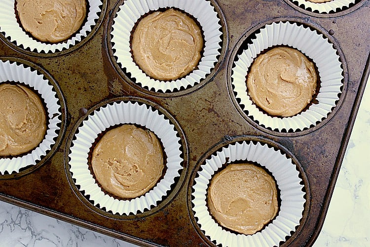 A muffin tin with paper liners, each with a layer of chocolate and peanut butter.