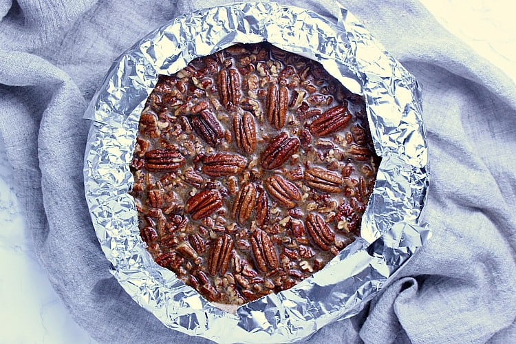 Pecan pie all ready to be baked. The edges are covered with tin foil.