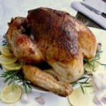 Whole roasted keto turkey on a serving plate, garnished with lemon slices, rosemary and cloves of garlic.