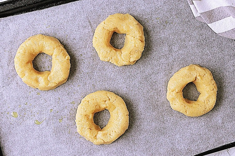 Baking sheet with parchment and 4 formed bagels.