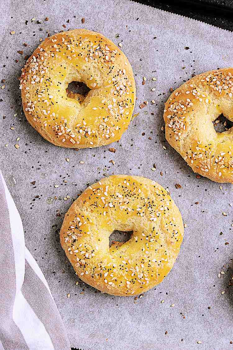Baking sheet with parchment and 3 fully baked bagels.