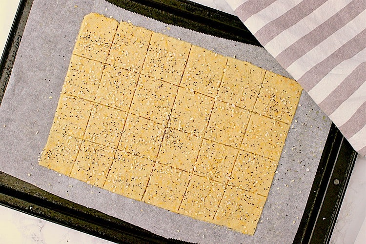 Crackers are on a baking sheet, sprinkled with everything but the bagel seasoning, and ready to be baked.