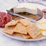 Appetizer plate with brie, cheddar, sausage, salami and a handful of Keto Crackers.