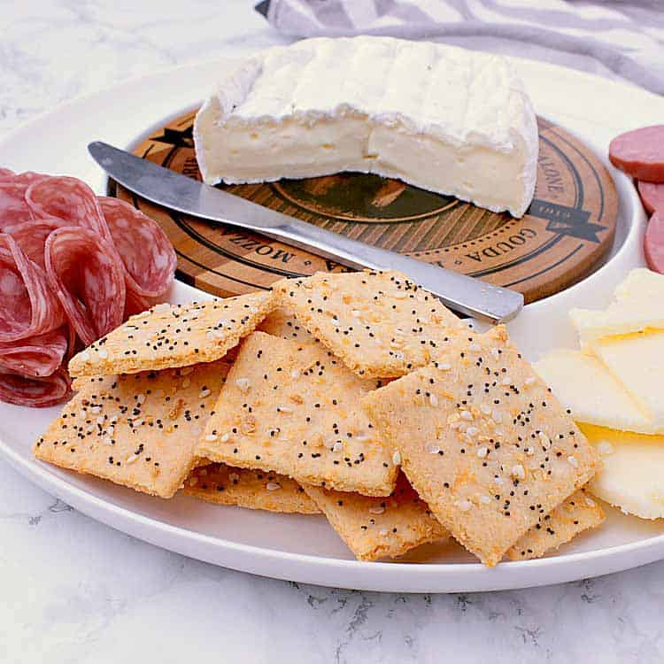 Snack platter with sausage, cheese slices, brie, salami, a knife and a handful of Keto Crackers.
