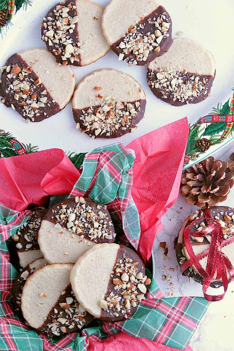 A tin with Christmas paper filled with Keto Shortbread Cookies, beside a wrapped stack of cookies and a Christmas plate filled with more cookies.