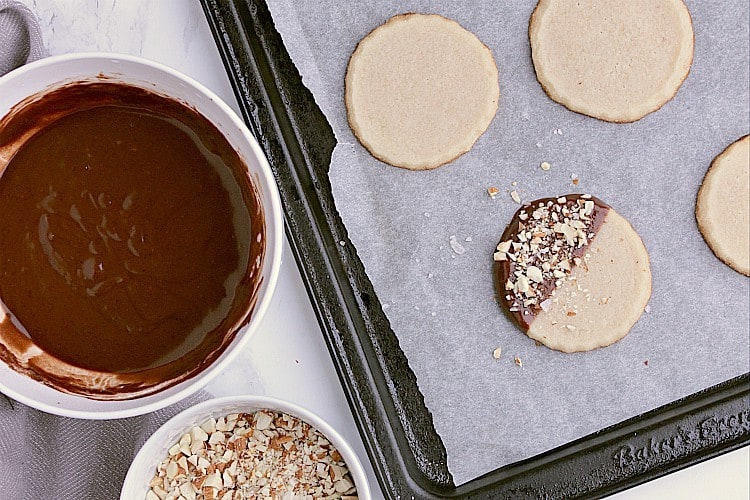 A baking sheet with cooled cookies, one has been dipped in chocolate and topped with almonds and sea salt. The baking sheet is beside a bowl of chopped almonds and another bowl of chocolate.