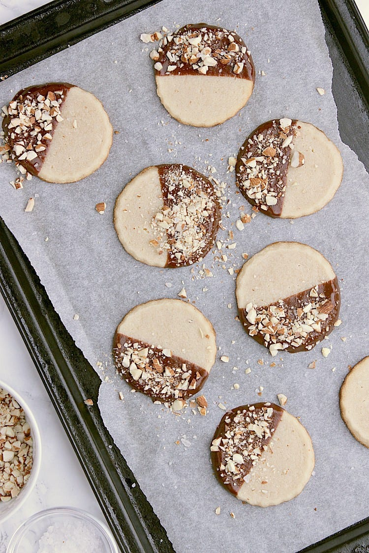 Baking sheet with Keto Shortbread Cookies that have been dipped in chocolate and sprinkled with chopped almonds and sea salt.