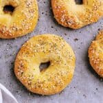 Four Keto Everything Bagels fresh from the oven, on a baking sheet.