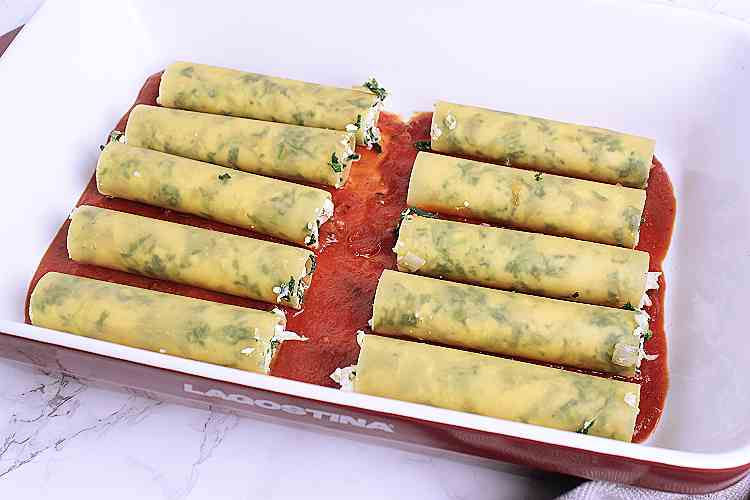 Stuffed cannelloni in a baking dish.