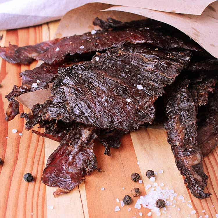 Wooden cutting board with a pile of Keto Beef Jerky.