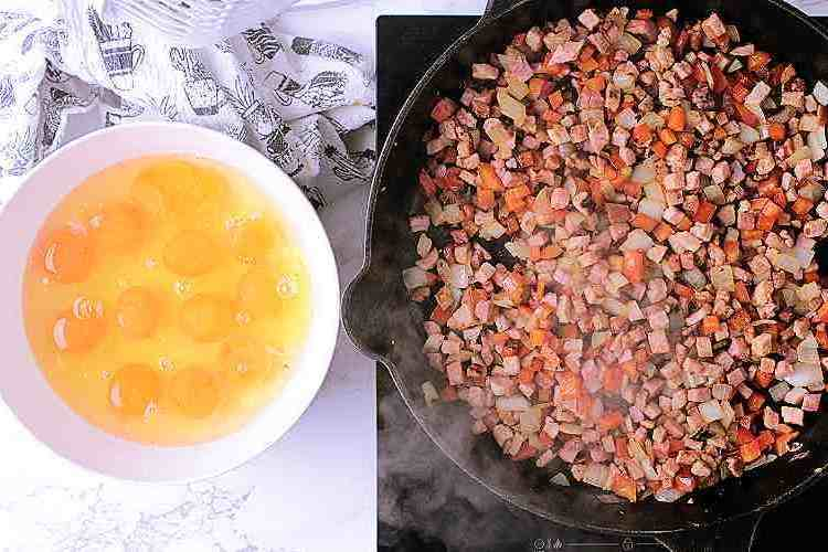 Cast iron skillet with cooked peppers, ham and onion next to a bowl with a dozen cracked eggs.