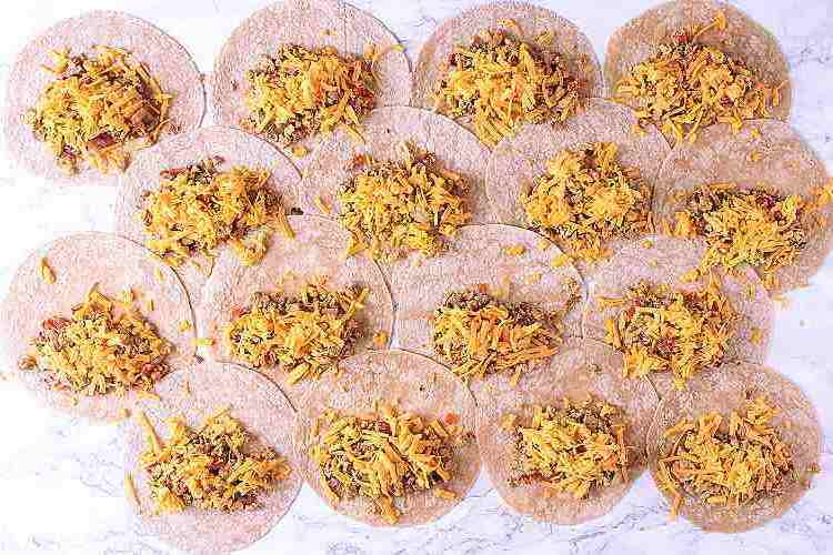 16 tortillas with scrambled eggs and shredded cheese on top.