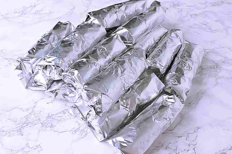 All of the Keto Breakfast Burritos wrapped in tin foil and stacked together.
