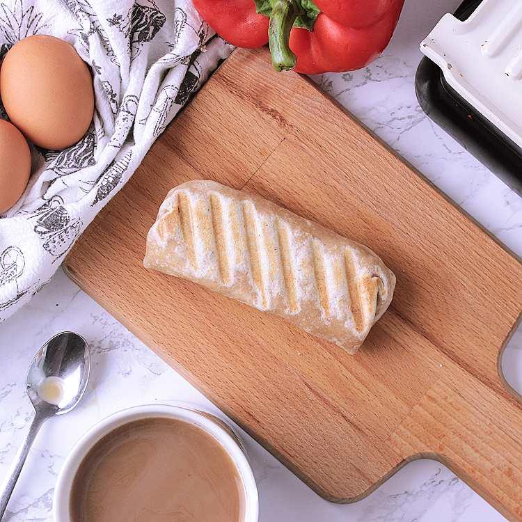 A wooden cutting board with a Keto Breakfast Burrito.