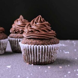 3 keto chocolate cupcakes with chocolate frosting.