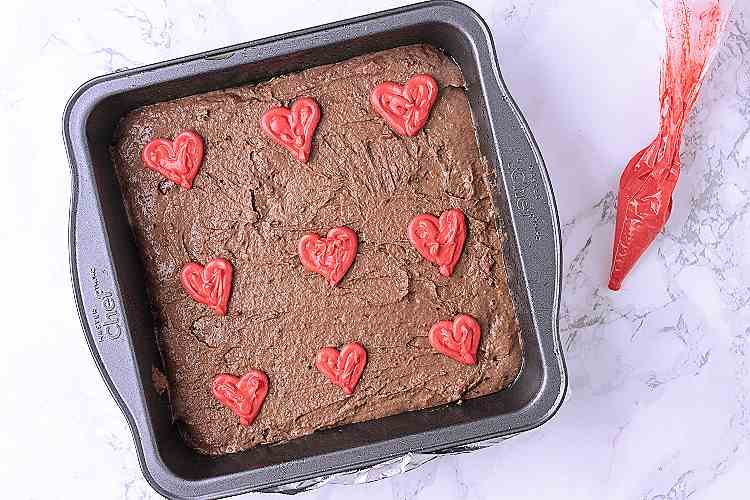 A baking dish with brownie batter and piped on red hearts.