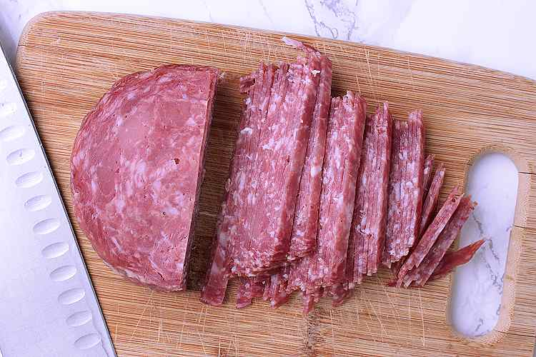 Wooden cutting board with chopped prosciutto salami.