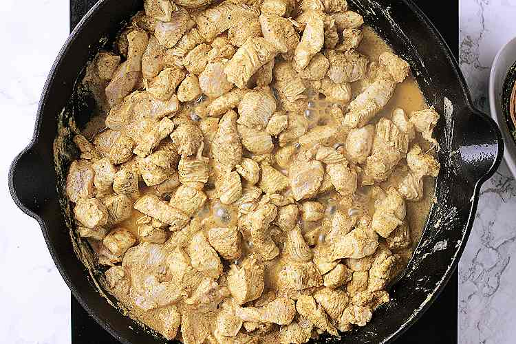 Iron skillet with cooked chicken.