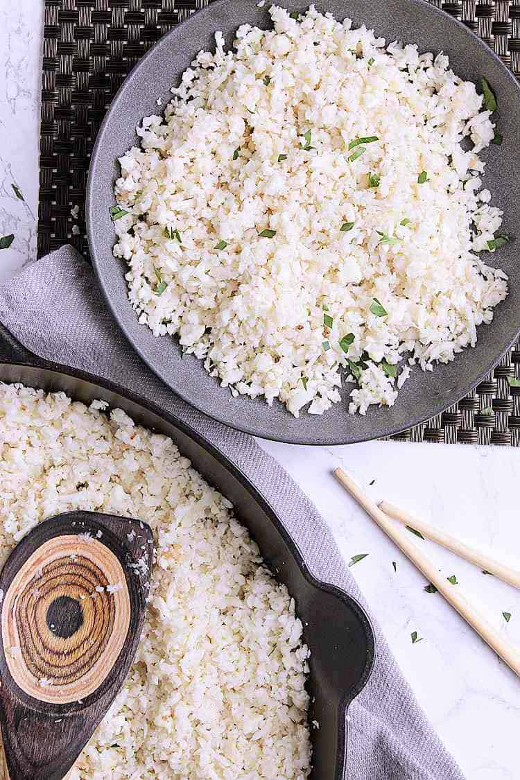 A bowl of cauliflower rice next to a cast iron skillet with cauliflower rice.