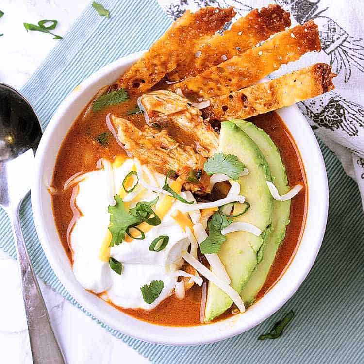 A bowl of Keto Chicken Tortilla Soup, garnished with avocado, sour cream, green onion, cilantro and cheese strips.