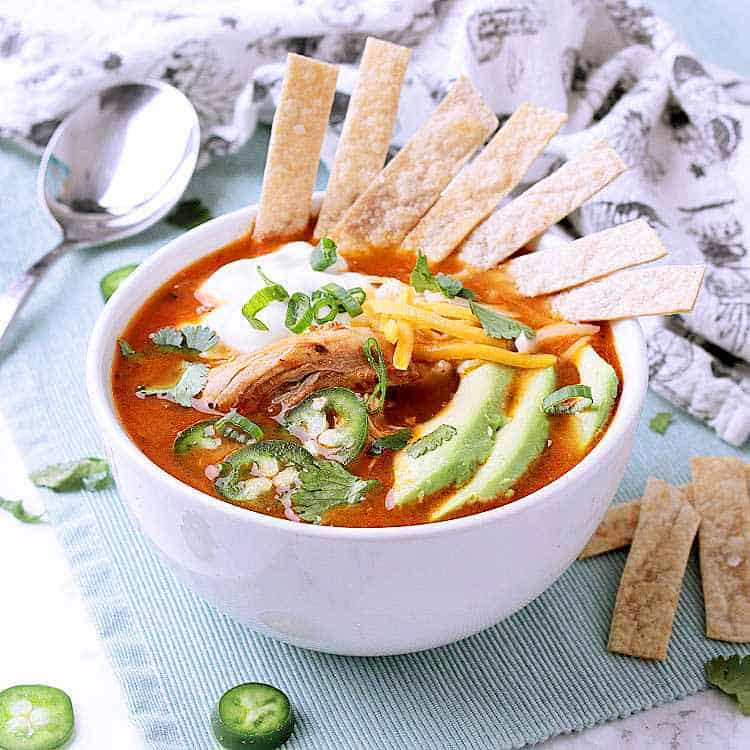 A white bowl with Keto Chicken Tortilla Soup, garnished with tortilla strips, sour cream, avocado, jalapeños and cilantro.