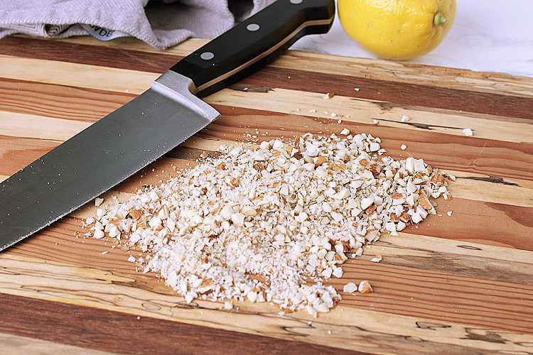 A wooden cutting board with minced almonds