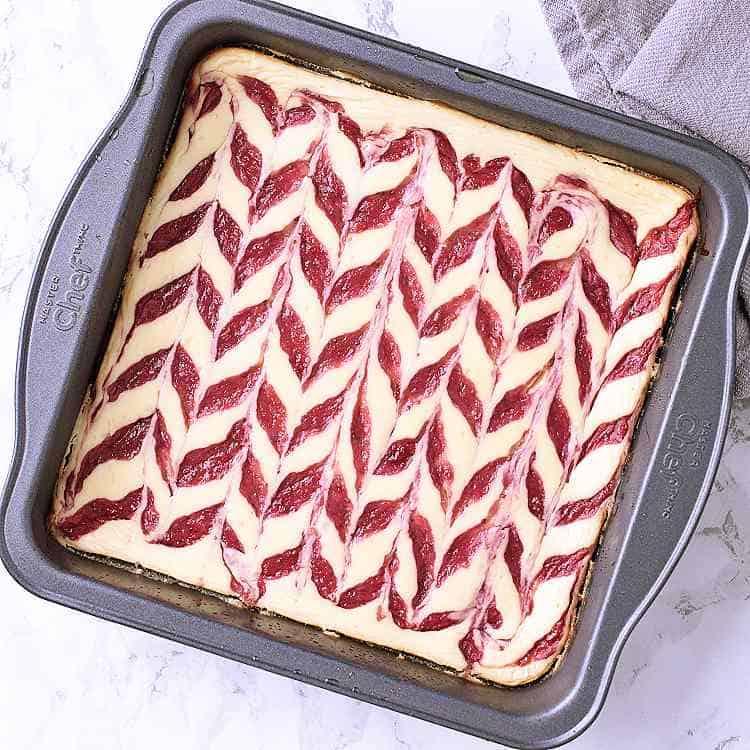 Fully baked Keto Strawberry Cheesecake, ready to be sliced into 9 bars.
