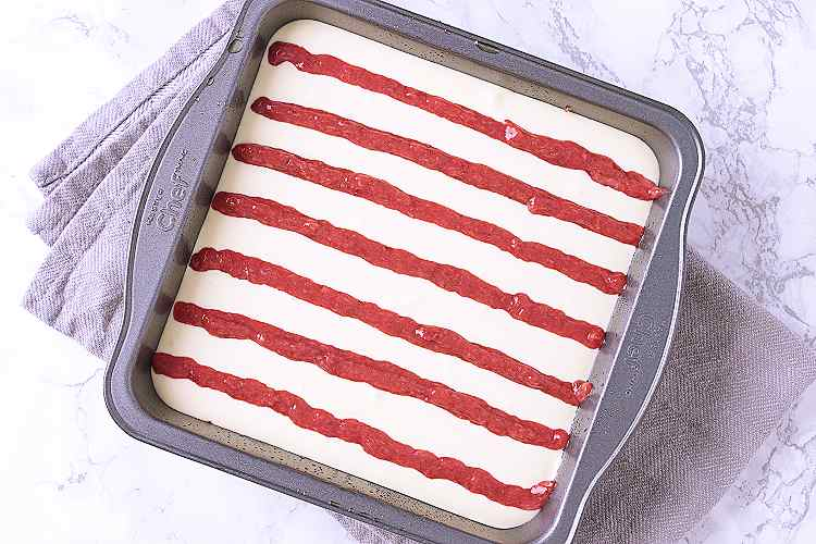 Unbaked cheesecake with vertical lines of strawberry sauce.