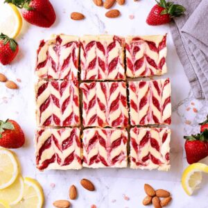 9 keto strawberry cheesecake bars surrounded by lemons, almonds and strawberries.
