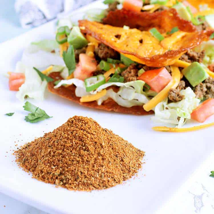 A pile of Keto Taco Seasoning in front of a couple of keto Tacos.