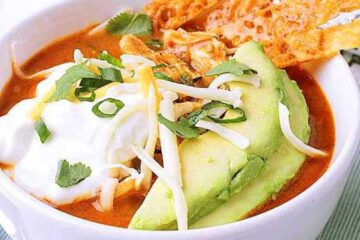 A white bowl with Keto Chicken Tortilla Soup topped with sour cream, cheese, avocado, cheese strips, cilantro and green onion.