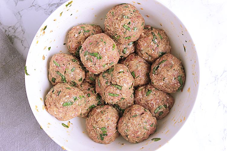 A white mixing bowl with 16 meatballs.