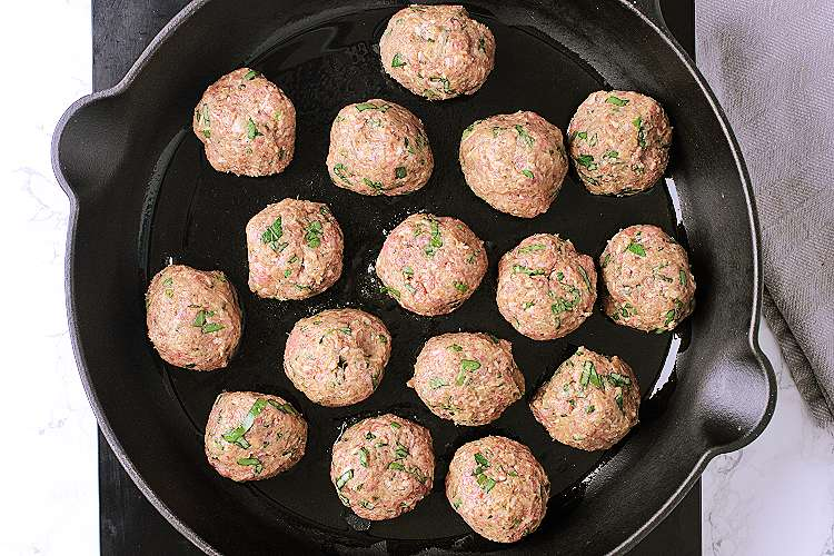 A cast iron skillet with 16 meatballs, evenly spaced throughout.