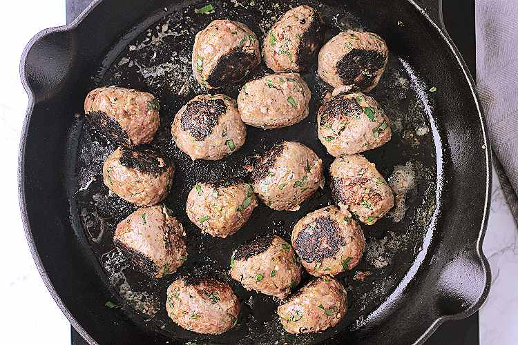 Cast iron skillet with 16 fried meatballs.