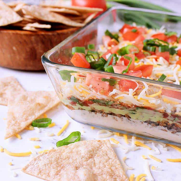 """9x13"""" glass dish layered with Keto Taco Dip, beside a bowl of low carb tortilla chips."""