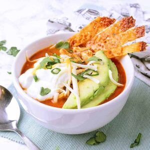 A white bowl with keto chicken tortilla soup and topped with sour cream, avocado and cheese strips.