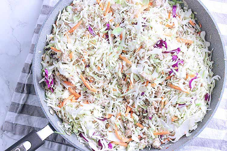 A skillet with cooked ground pork and coleslaw.