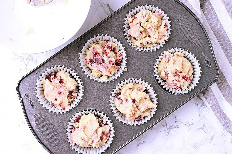 A muffin tin lined with paper cups and filled with Keto raspberry muffin batter.