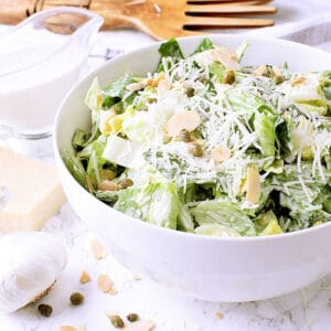 A white bowl with Keto Caesar Dressing, garnished with parmesan cheese.