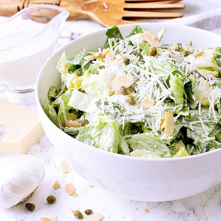 A big white bowl of Keto Caesar Salad, garnished with extra parmesan, almonds and capers.